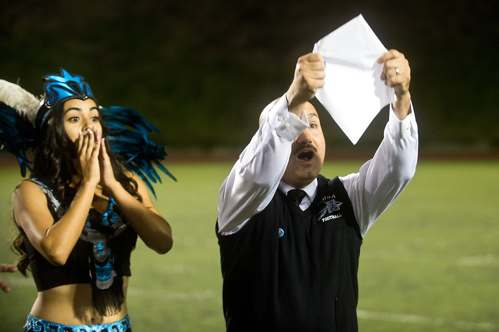 Description of . Principal Ramiro Rubalcaba unveils the name of Azusa High 2013 Homecoming Queen during halftime of the homecoming game at Citrus College Stadium in Glendora on Friday night, Sept. 27, 2013.( Photo by Watchara Phomicinda/ San Gabriel Valley Tribune)