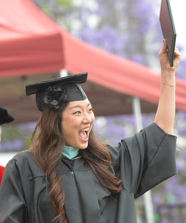 Description of . Jinny Shim shows her diploma to a cheering family during the Commencement Ceremony at Biola University in La Mirada on Friday May 23, 2014. Kay Warren, International speaker and author, gives the commencement address. (Photo by Keith Durflinger/Whittier Daily News)
