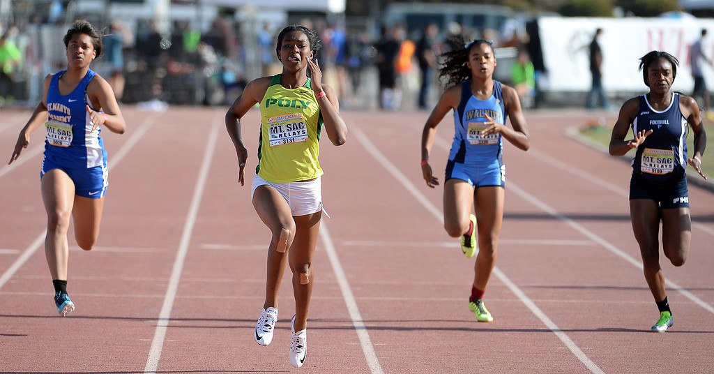 Description of . Long Beach Poly's Ariana Washington, center, wins the 200 Dash Invitational during the Mt. SAC Relays in Hilmer Lodge Stadium on the campus of Mt. San Antonio College in Walnut, Calif., on Saturday, April 19, 2014. 