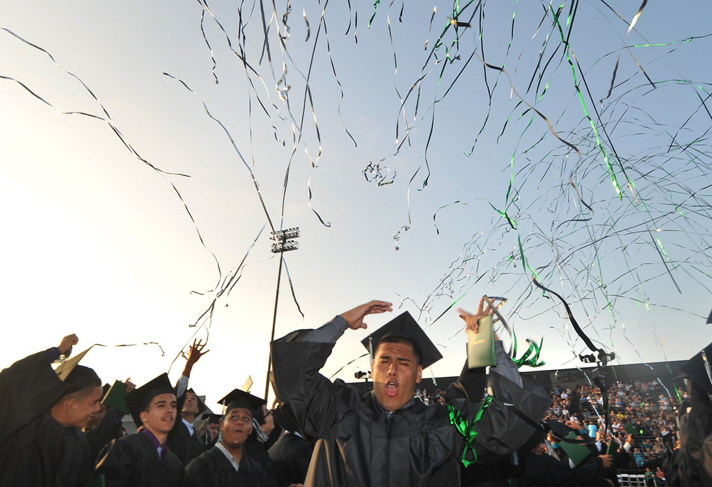 Description of . Jesus Garnica celebrates with classmates on the field during the 53rd Commencement at Pioneer High School in Whittier on Wednesday June 12, 2013. (SGVN/Staff Photo by Keith Durflinger)