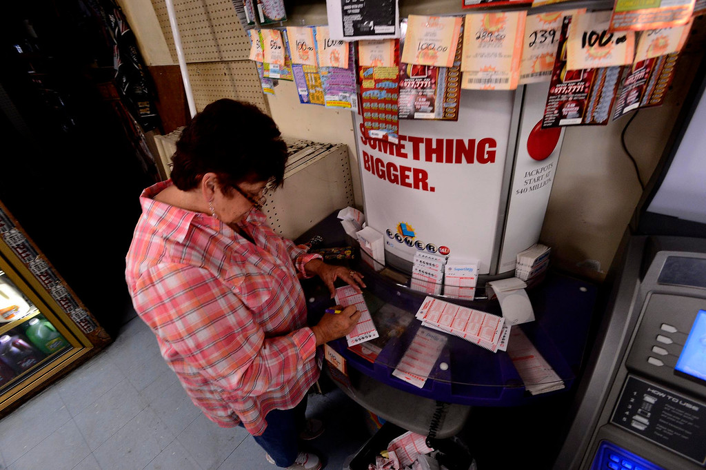 Description of . Gloria Ybarra, of Fontana, buys a Powerball ticket at Quicker Liquor along Sierra Avenue in Fontana May 17, 2013.  The Powerball Lottery, which California just joined earlier this year, is at $600 million for Saturday's drawing.  It is the third-highest jackpot in U.S. history.  GABRIEL LUIS ACOSTA/STAFF PHOTOGRAPHER.