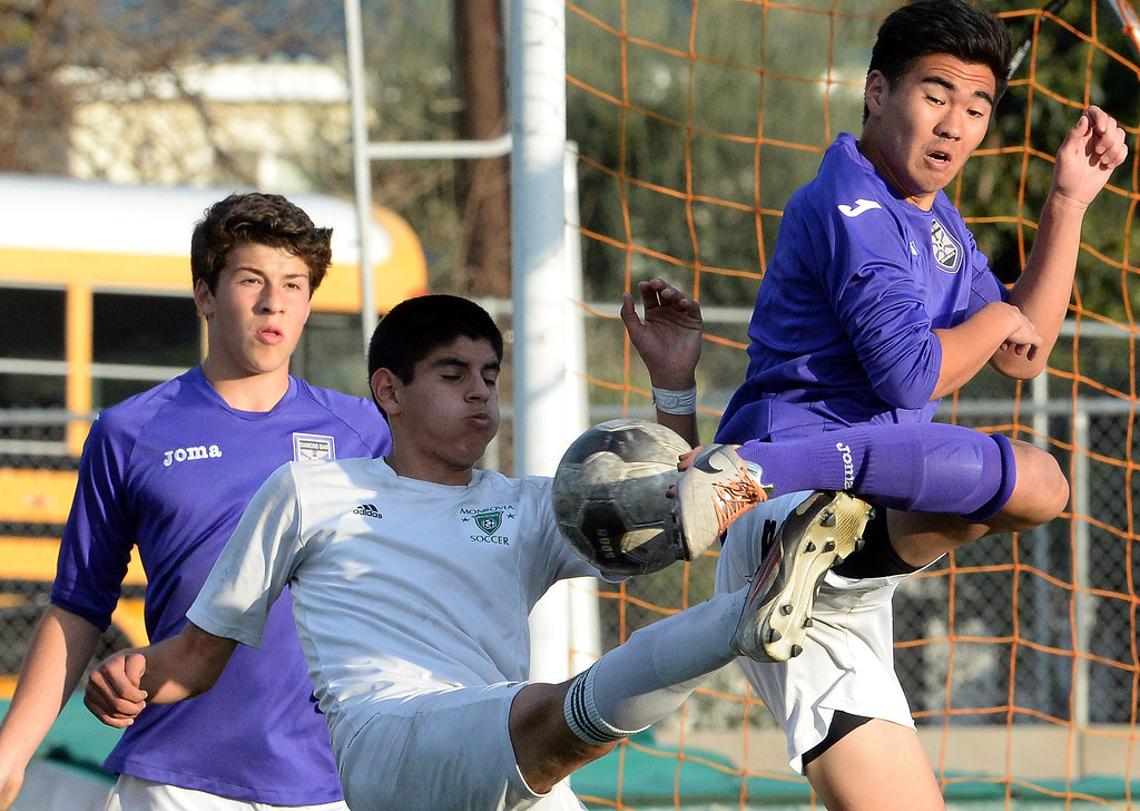 Description of . Monrovia's Joel Cortez, center, and Diamond Bar's Edward Park, right, kicks the ball in the second half during a second round soccer match at Monrovia High School in Monrovia, Calif., on Tuesday, Feb.25, 2014. Diamond Bar won 3-2 on penalty kicks.