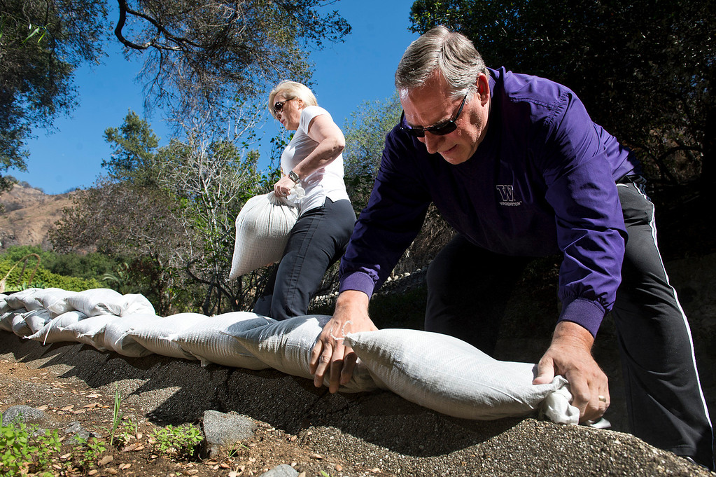 Description of . Homeowners Lizette and Tom Verti stack sandbags behind their home in 1100 block of Englewild Drive in Glendora on Tuesday, Feb. 25, 2014. The couple are preparing for two major rainstorms that will hit the region this week that potentially will cause mudslides in the area devastated by the Colby Fire. (Photo by Watchara Phomicinda/ San Gabriel Valley)