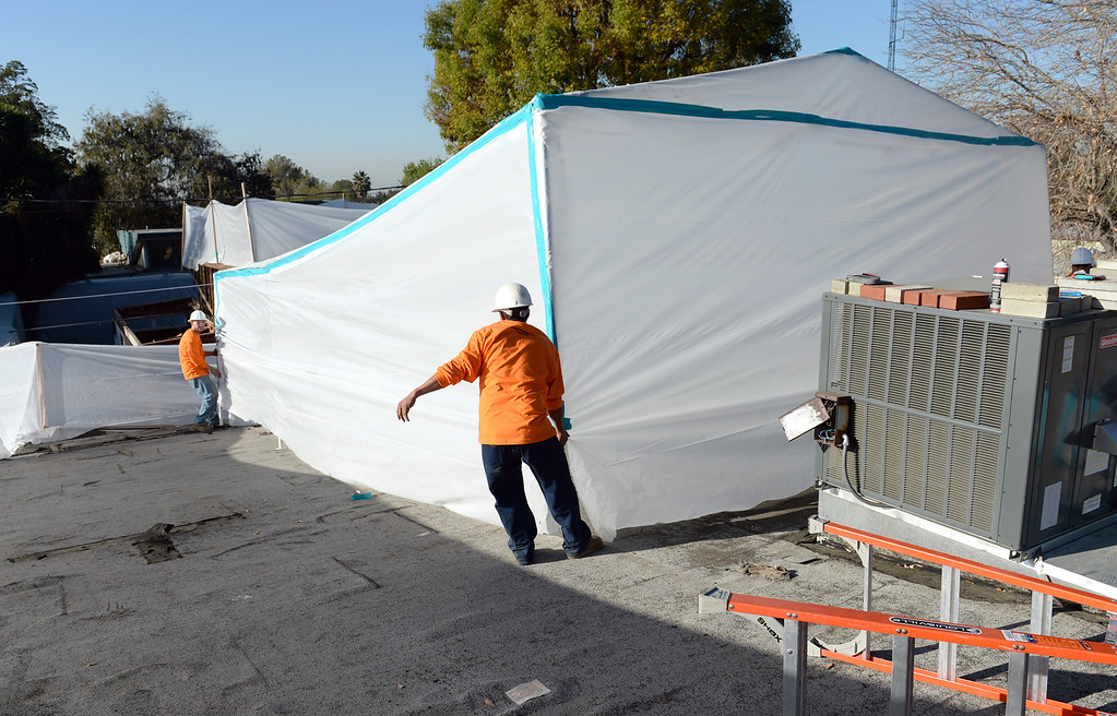 Description of . Workers set up an isolation tent as Asbestos is being removed by Resource Environmental, Inc. from La Habra Heights City Hall on Wednesday January 22, 2014. More asbestos was found in the roofing material last week. (Staff Photo by Keith Durflinger/Pasadena Star-News)