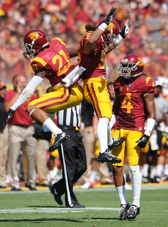 Description of . USC #21 Su's Cravens #56 Anthony Sarao and #4 Torin Harris celebrate in the 3rd quarter. USC defeated Boston College 35-7 in a game played at the Coliseum in Los Angeles, CA. 9/14/2013. photo by (John McCoy/Los Angeles Daily News)