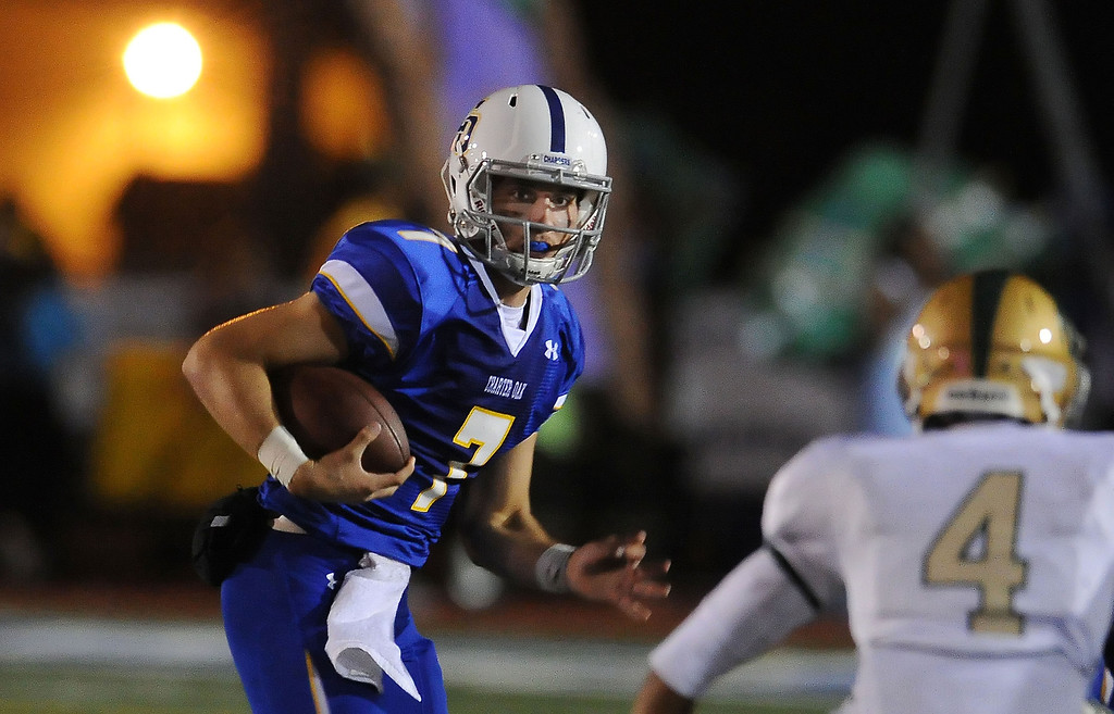Description of . Charter Oak quarterback Kory Brown (7) scrambles past Damien's Leroy Cloud (4) in the first half of a prep football game at Charter Oak High School in Covina, Calif., Friday, Oct. 11, 2013.    (Keith Birmingham Pasadena Star-News)