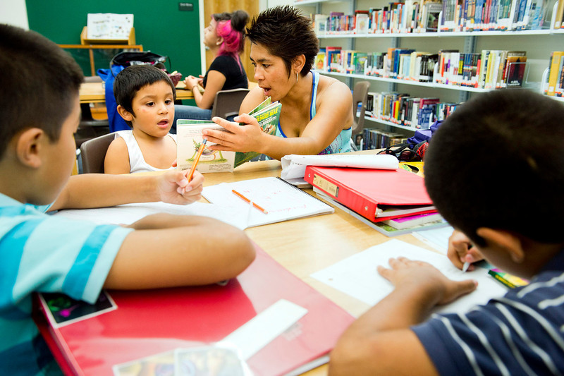 Angel Diaz Mejia, 8, reads a book with mom, Cristina Mejia, during the after school community program at the new Nogales High School library in La Puente on Tuesday, Aug. 30, 2013. The after school program provides homework help from 3 to 5 p.m. for students in grades K-6, plus a free computer lab, storytime and activities. (Staff photo by Watchara Phomicinda/ San Gabriel Valley Tribune)