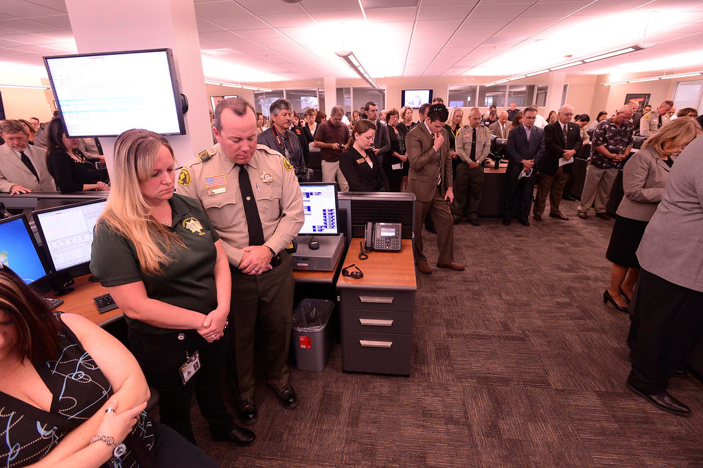 Description of . Dispatch operator Shelby Moore, left, and husband Deputy Robert Moore, bow in prayer at the start of the dedication ceremony for the High Desert Public Safety Operations Center in Hesperia May 10, 2013.  GABRIEL LUIS ACOSTA/STAFF PHOTOGRAPHER.