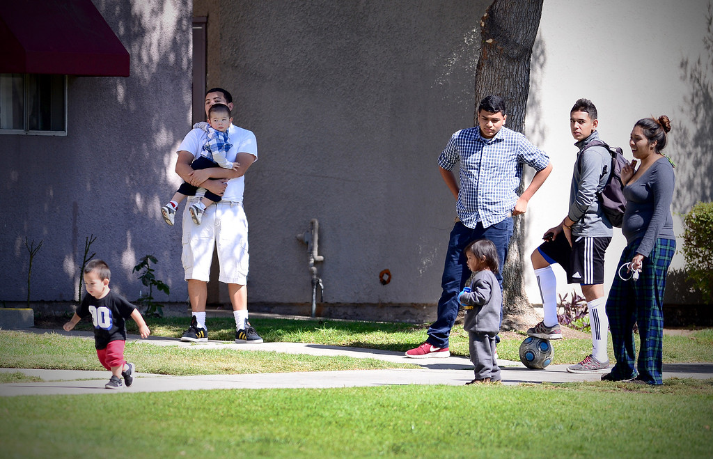 Description of . People socialize at Kings Village apartments in Pasadena  as Pasadena Police investigate an officer involved shooting at the complex Friday, October 11, 2013. (Photo by Sarah Reingewirtz/Pasadena-Star News)