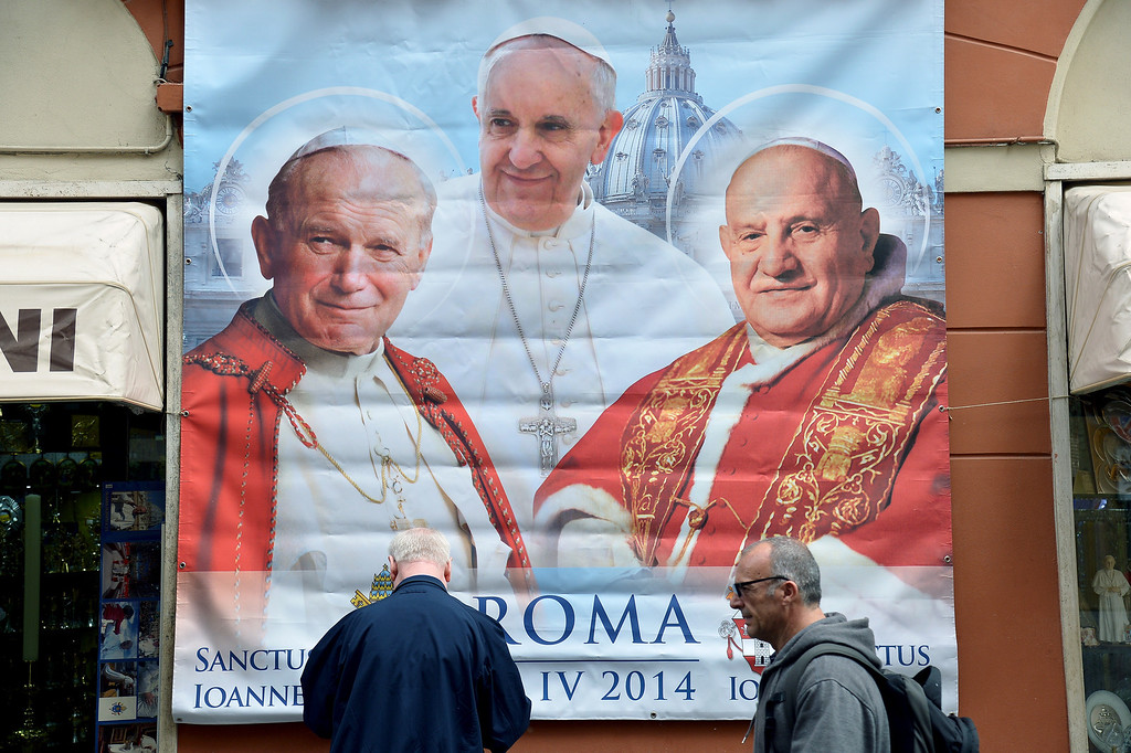 Description of . A poster showing Pope Francis middle pope John Paul II (L) and Pope John XXIII (R), that will be canonized next Sunday, is seen in Borgo Pio street near the Vatican during the pontiff weekly general audience in St. Peter's square on April 23, 2014.                (ALBERTO PIZZOLI/AFP/Getty Images)
