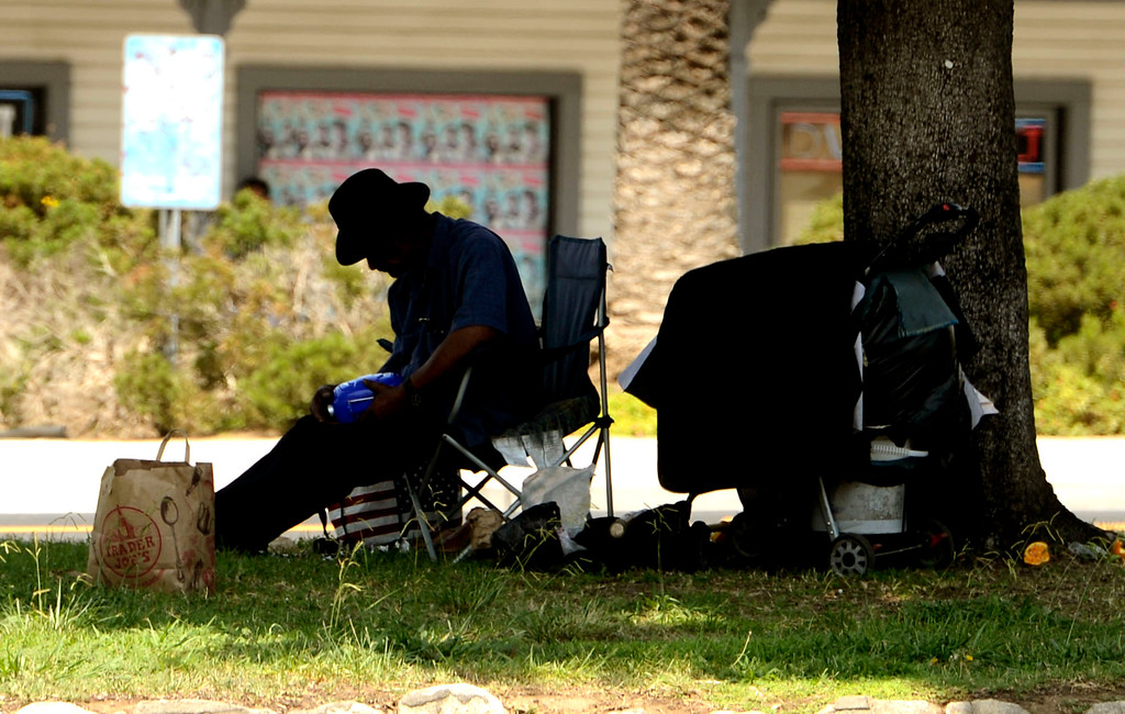 Description of . A homeless man sits in the center divider of East Colton Avenue in Redlands August 16, 2013.  Homelessness has become a large problem in the San Bernardino County area. GABREL LUIS ACOSTA/STAFF PHOTOGRAPHER.