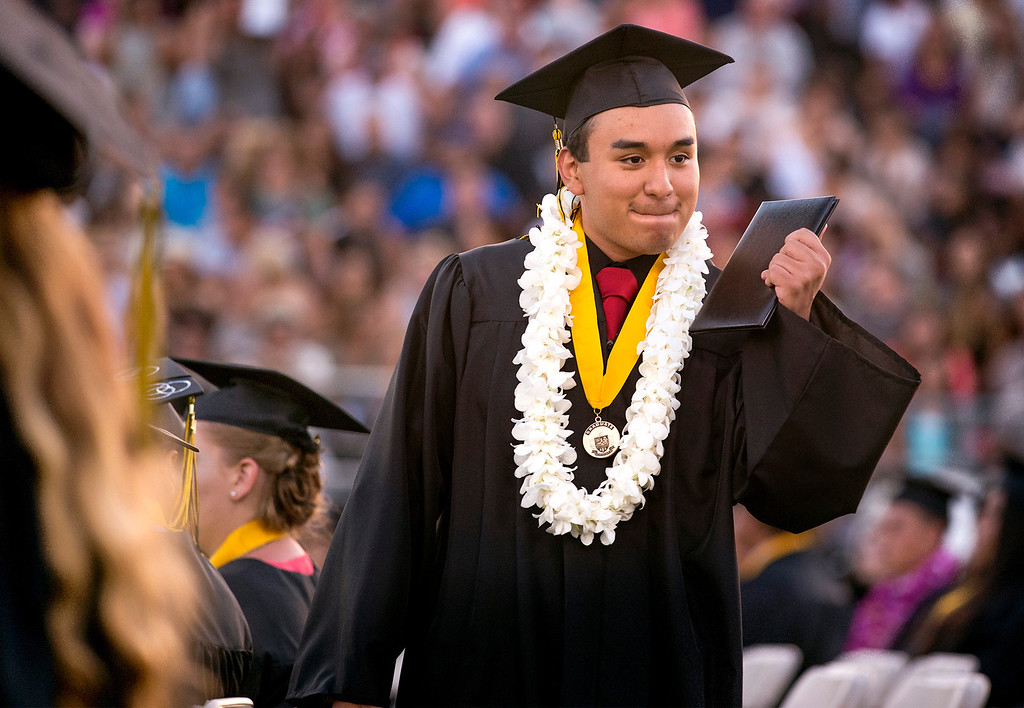 Description of . Rafael Meza shows off his diploma to friends during Northview High graduation commencement at Covina District Field June 11, 2014.   (Staff photo by Leo Jarzomb/San Gabriel Valley Tribune)
