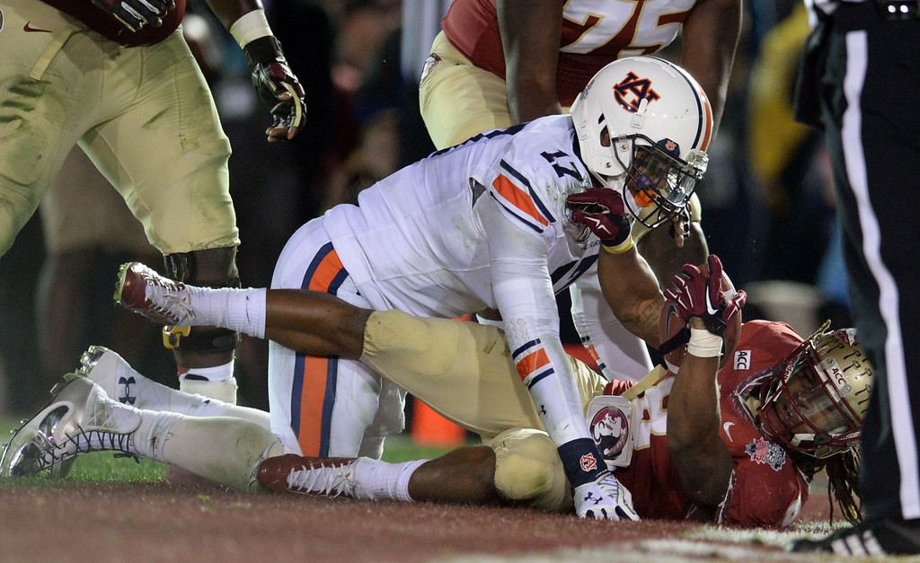 Description of . Florida State running back Devonta Freeman (8) dives a touchdown past Auburn linebacker Kris Frost (17) in the first half of the BCS National Championship game at the Rose Bowl in Pasadena, Calif., on Monday, Jan. 6, 2014.   (Keith Birmingham Pasadena Star-News)