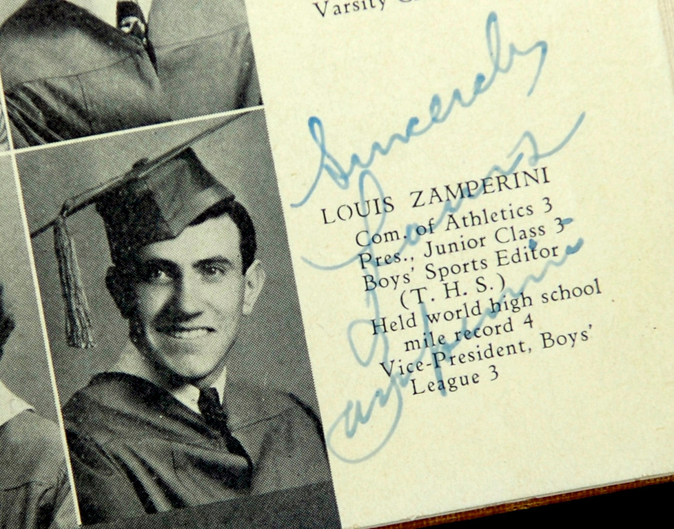 Description of . TORRANCE - 01/27/07 - DAILY BREEZE PHOTO: SCOTT VARLEY - Torrance High and graduate Louis Zamperini celebrate their 90th birthdays Saturday at the school. 1935 graduate Julian Isen brough his yearbook with Zamerini's picture and signature. (1/27/07)  (Photo by Scott Varley/Daily Breeze)