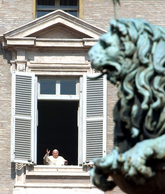 Description of . Pope John Paul II is framed by a bronze lion as he blesses pilgrims and faithful during a surprise appearance at the open window of  his studio overlooking St. Peter's Square at the Vatican, Wednesday, March 16, 2005. This is the first time he has been seen since  his release from hospital Sunday March 13. (AP Photo / Massimo Sambucetti)