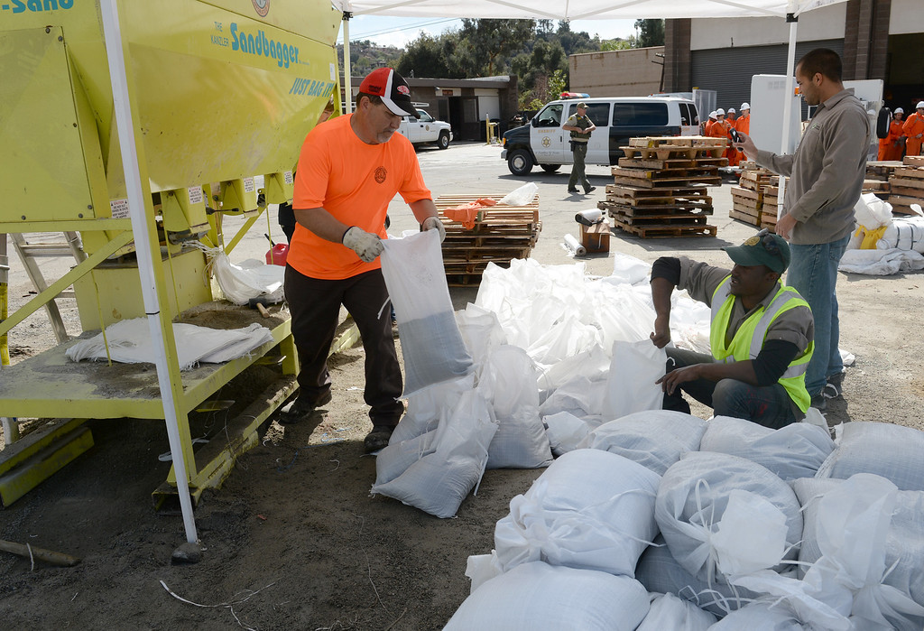 Description of . Workers fill up sandbags at the Glendora City Yard for residents in Glendora on Thursday February 27, 2014. (Staff Photo by Keith Durflinger/San Gabriel Valley Tribune)