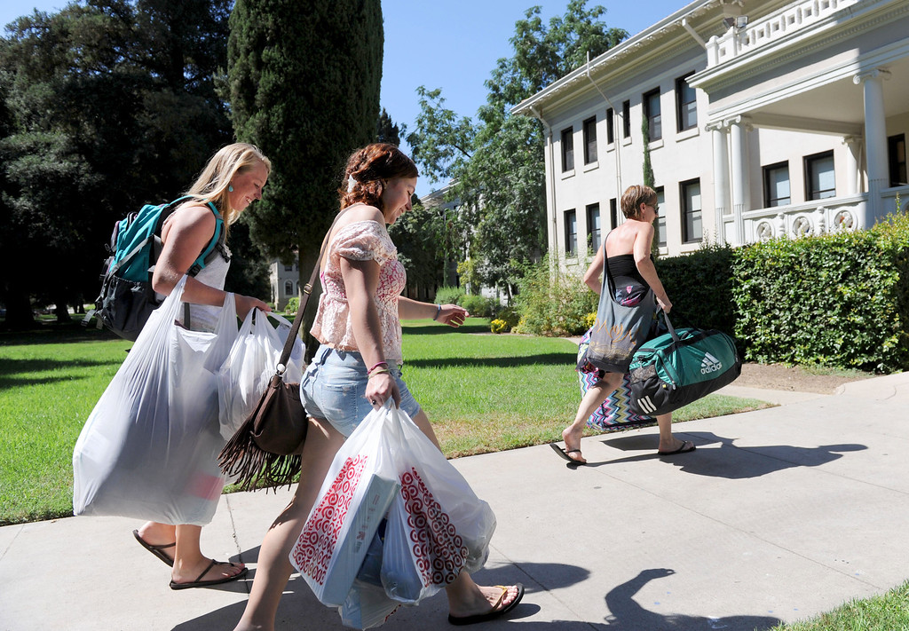 Description of . (John Valenzuela/Staff Photographer) Students Erin Gaffney (left) and Sydney Finkbohner (right) move their belonging into the Fairmont dorm, with helps from Lynn Finkbohner, Wednesday moring during move-in day at the University of Redlands, August 28, 2013.