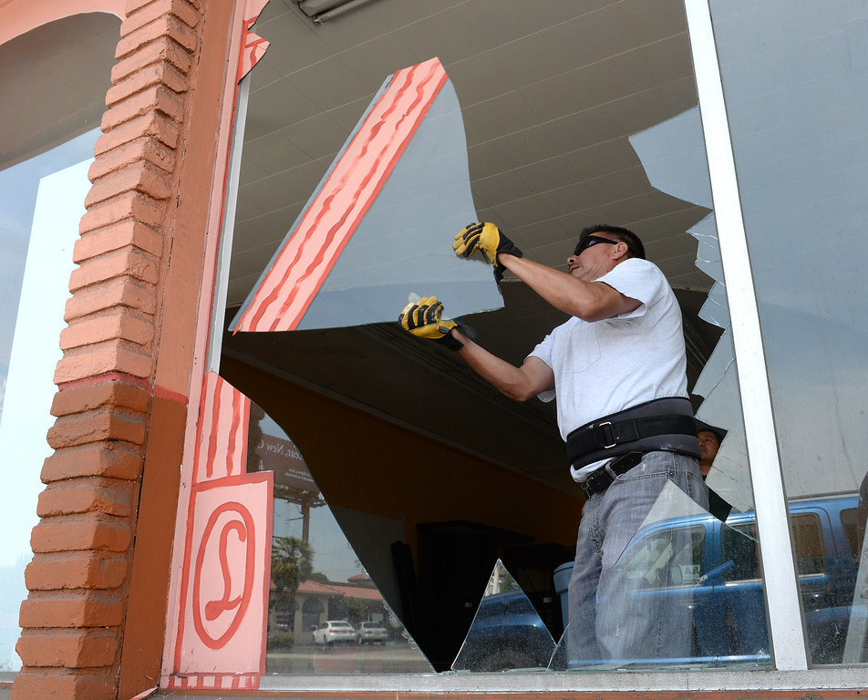 Description of . Martin Jimenez cleans up broken glass from a front window of a former tile store after the 5.1 earthquake centered in La Habra on Saturday March 29, 2014. (Staff Photo by Keith Durflinger/Whittier Daily News)