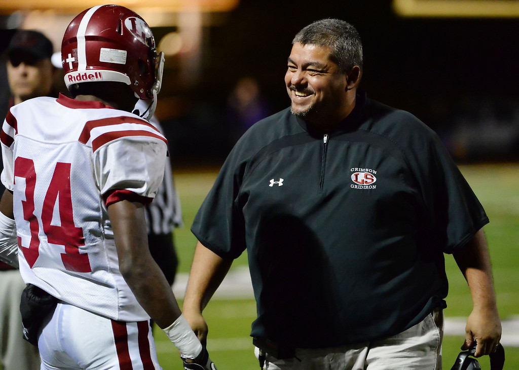 Description of . La Serna head coach Margarito Beltran smiles after a touchdown in the first half of a CIF-SS playoff football game against Diamond Bar at Diamond Bar High School in Diamond Bar, Calif., on Friday, Nov. 22, 2013.   (Keith Birmingham Pasadena Star-News)