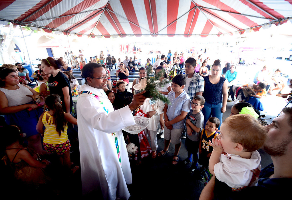 Description of . Father Lambert Okere blesses children before the Blessing of the Animals during their 242nd Annual La Fiesta de San Gabriel Saturday, August 31, 2013 at the San Gabriel Mission. The fiesta runs through Sunday. (Photo by Sarah Reingewirtz/Pasadena Star-News)