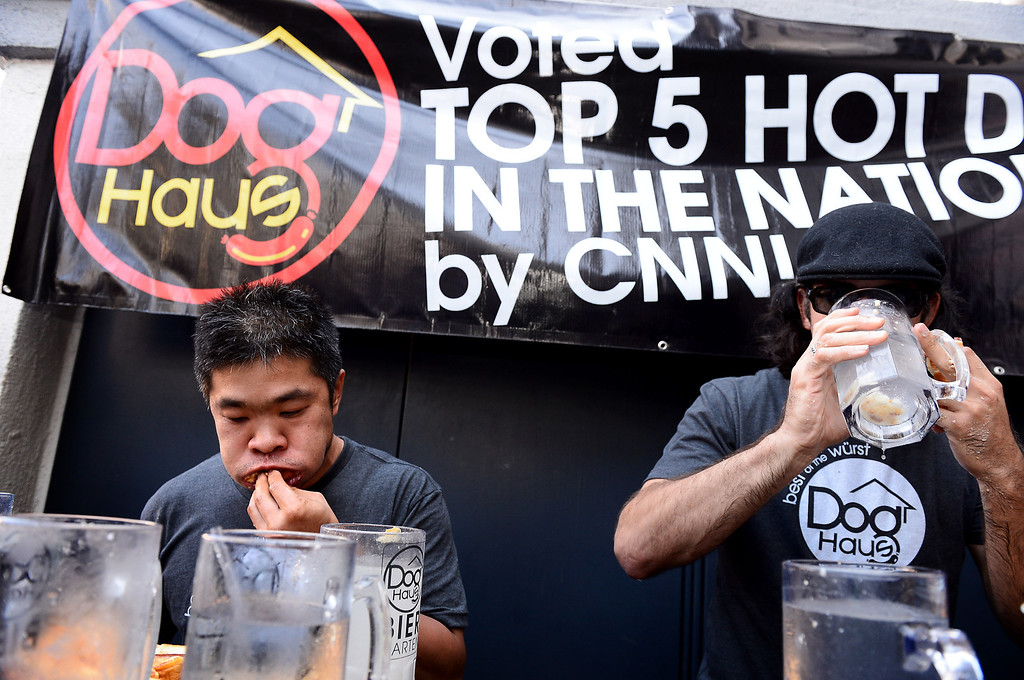 Description of . Jimmy Lin and Naader Reda, of Victorville, compete in a tiebreaker during the First Annual Hot Dog Eating Competition at Dog Haus Biergarten in Old Pasadena Saturday, July 6, 2013. Jimmy Lin won after eating 11 dogs, 3 during a tiebreaker. (SGVN/Staff Photo by Sarah Reingewirtz)