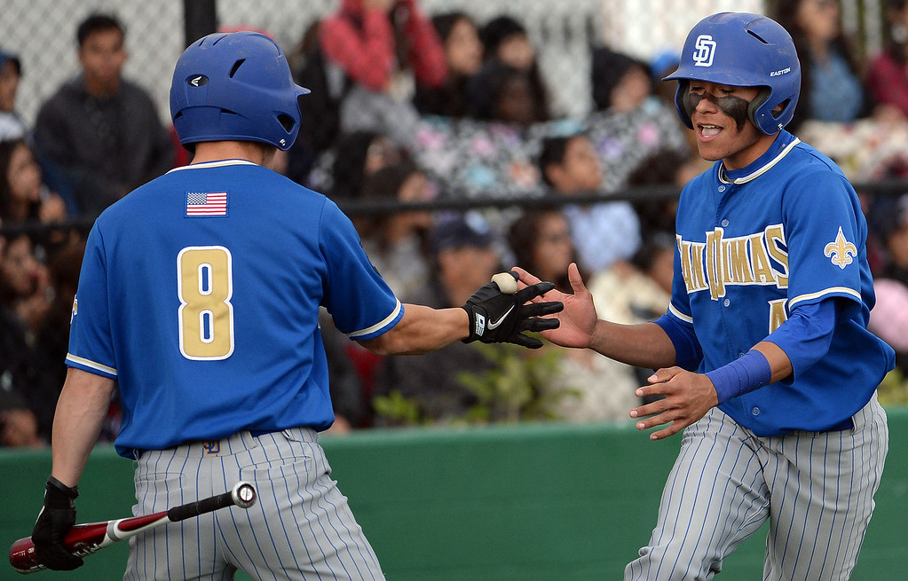 Description of . San Dimas' Jeremy Marquez (4) high fives teammate Daniel Millwee (C) (8) after scoring on a double by San Dimas' David Vargas (not pictured) in the sixth inning of a prep baseball game at Northview High School in Covina, Calif., on Wednesday, March 26, 2014. San Dimas won 2-0.