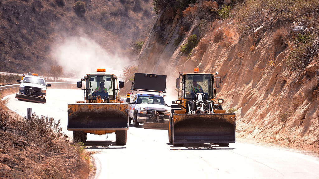 Description of . CalTrans bulldozers clear debris left behind from the Silver Fire as seen along Highway 243 in the mountains south of Banning August 10, 2013.   GABRIEL LUIS ACOSTA/STAFF PHOTOTGRAPHER.