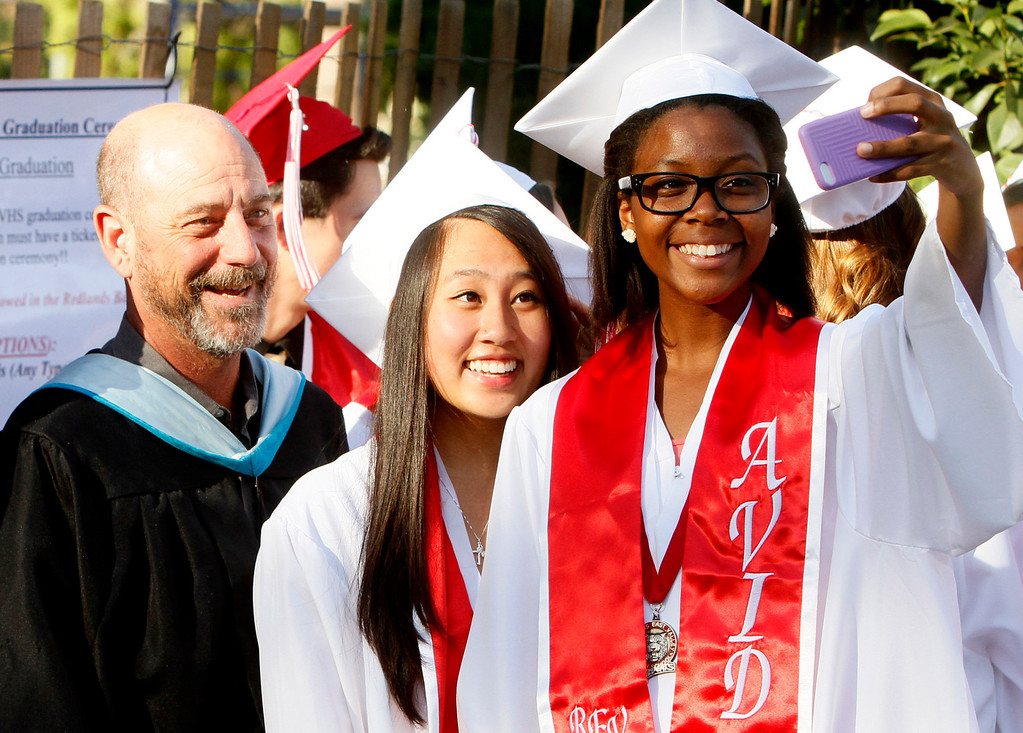 Description of . Redlands East Valley High School graduates Vanessa Skinner, right, and Cindy Song take a selfie with teacher Sam Patalano prior to the start of the class of 2014 graduation ceremony on Thursday, June 12, 2014 at the Redlands Bowl in Redlands, Ca.  (Photo by Micah Escamilla/Redlands Daily Facts)