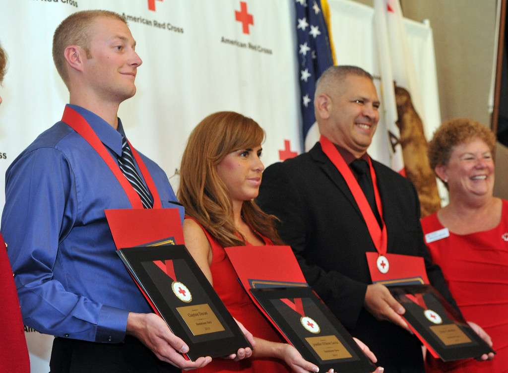 Description of . Clayton Duran, Jennifer Garcia and Jesse Cabadas are honored for their quick action in assisting a Sheriff's Cadet from the Sheriff's Training Academy in Whittier as the Rio Hondo Chapter of the American Red Cross honors 14 people for their part in performing extraordinary acts during their Hometown Heroes luncheon at the Quiet Cannon in Montebello on Thursday June 27, 2013. (SGVN/Staff Photo by Keith Durflinger)