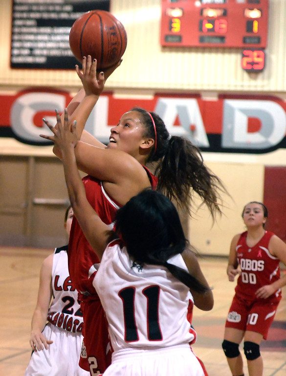 Description of . Workman's Alize Williams drives to the basket past Gladstone's Tiara Rice (11) in the first half of a prep basketball game at Gladstone High School in Covina, Calif., on Friday, Jan. 17, 2014. (Keith Birmingham Pasadena Star-News)