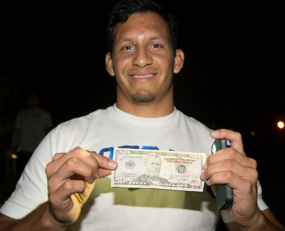 Description of . Michael Villamontes shows the pez dispenser he found with $50 as cash hunters search all over Penn Park in Whittier for #HiddenCash stashed in Pez dipsensers and lunch boxes in the park bushes on Thursday July 10, 2014. Hundreds of people searched through the bushes all over the park. (Staff Photo by Keith Durflinger/Pasadena Star-News)