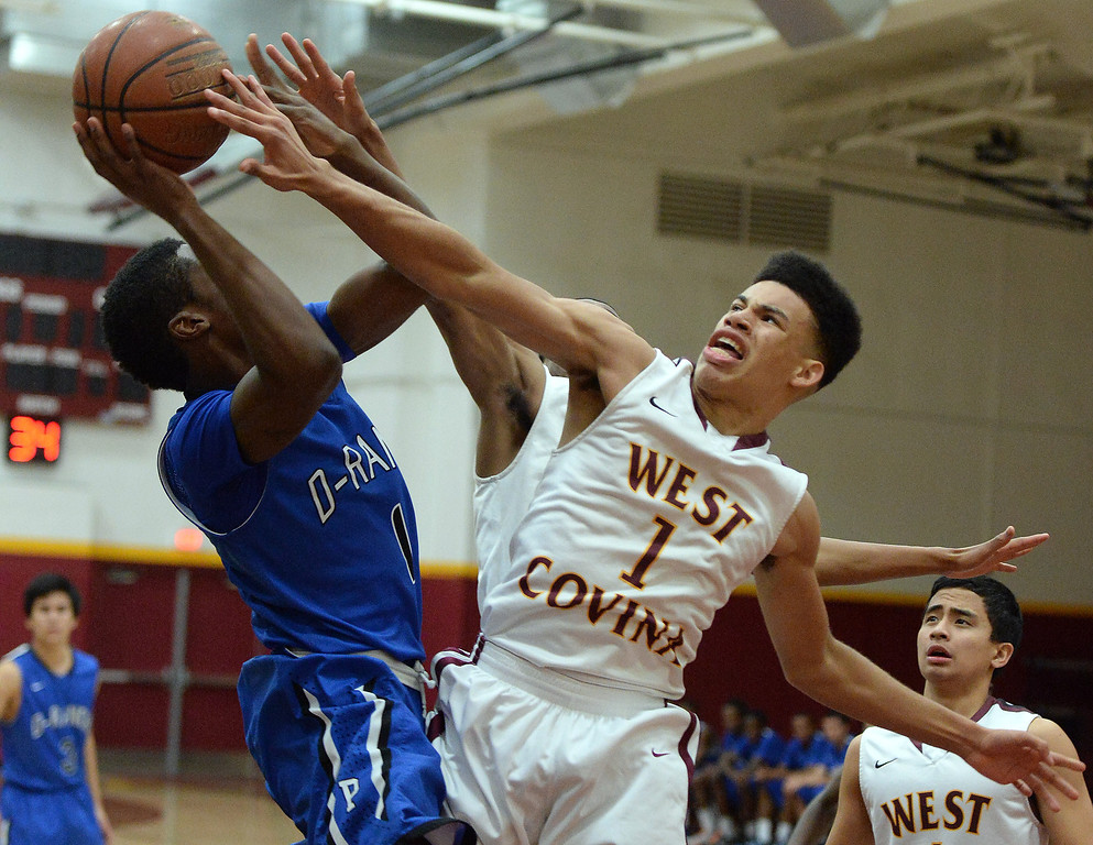 Description of . Diamond Ranch's Ernest Ugoagu (1) drives to the basket as West Covina's Michael Fallon (1) defends in the first half of a prep basketball game at West Covina High School in West Covina, Calif., on Wednesday, Jan. 8, 2014. (Keith Birmingham Pasadena Star-News)