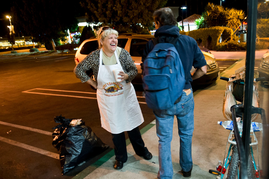 Description of . Nicolette Wingert, left, chats with a homeless man in Glendora on Wednesday night, Nov. 27, 2013. Nicolette Wingert has been feeding the homeless six days a week for the past seven years with Nurses4Christ, a nonprofit organization she founded in 2006. She and Phillip Stern of Glendora have been going every day since 2008, feeding homeless people sandwiches and hot food; giving them bottles of water, clothes and blankets. (Photo by Watchara Phomicinda/San Gabriel Valley Tribune)