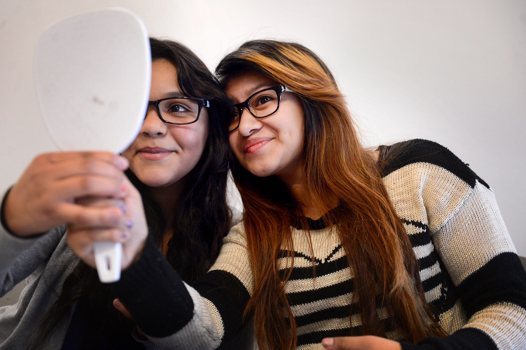 Description of . From left, Cyndy Lopez and Yesenia Garcia, both 15 and 10th graders at Montebello Unified School District's Applied Technology Center (ATC) High School, choose free eye glasses from Helen Keller's International ChildSight Los Angeles program Friday, February 7, 2014. The group has screened 15,000 students in Los Angeles County with 2,000 receiving glasses. (Photo by Sarah Reingewirtz/Pasadena Star-News)