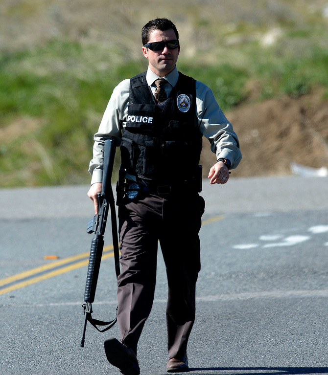 Description of . A Redlands Police officer at a police blockade at Highway 38 and Bryant Street near the Mill Street Ranger Station west of Yucaipa February 12, 2013.  Authorities believe that they exchanged gunfire with fugitive Christopher Dorner in the Barton Flats area of the San Bernardino National Forest.  Fish and Game officers spotted a man fitting the description of Dorner driving a white pick-up. (Staff photo by Gabriel Luis Acosta/The Sun)