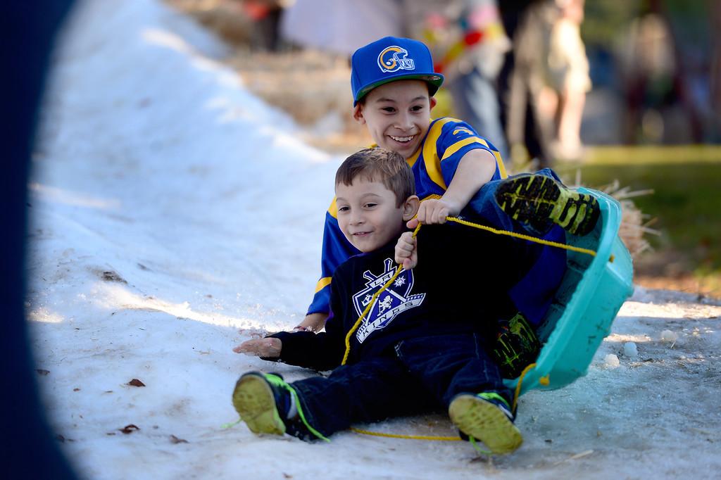 Description of . Roland Espinoza, 4 and his brother Danny, 9, of East Los Angeles go sledding during Montebello's annual Winter Wonderland at Montebello City Park Saturday, December 14, 2013. (Photo by Sarah Reingewirtz/Pasadena Star-News)