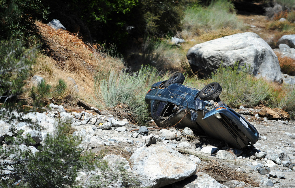 Description of . Sunday's storm washed resident Andrew Waton's car into a creek 200 yards behind his home as seen here on Monday, August 4, 2014 in Forest Falls, Ca. (Micah Escamilla/San Bernardino Sun)