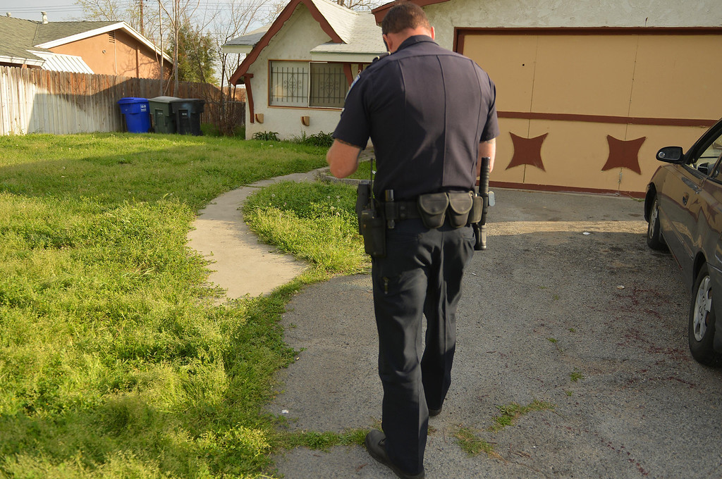 Description of . San Bernardino Police Officer Chris Flowers, investigates the scene where a man was shot multiple times, Wednesday March 5, 2014, after pulling into his driveway in the 2000 block of West Gilbert Street, San Bernadino. (Photo by LaFonzo Carter/The Sun)