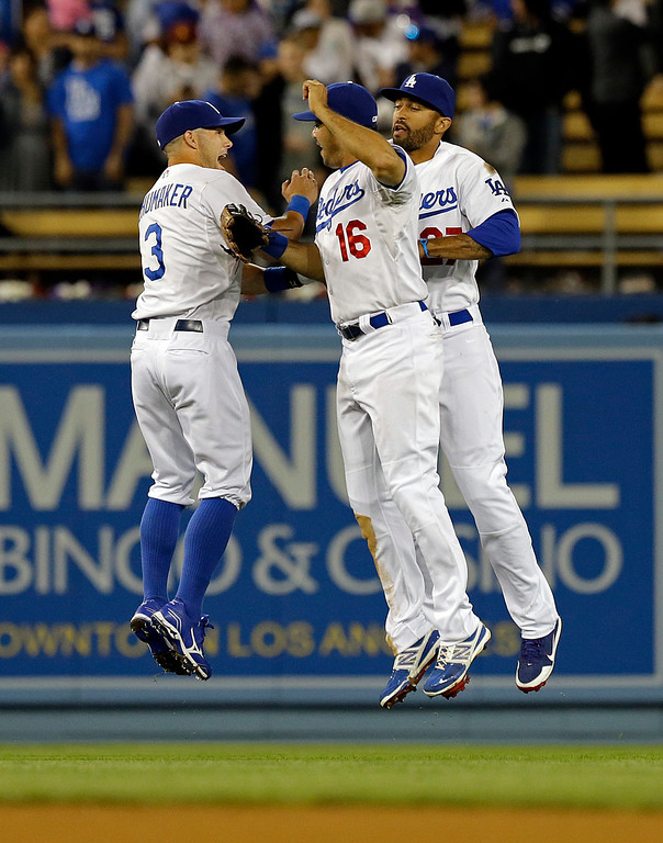 Description of . Los Angeles Dodgers outfielders, from left, Skip Schumaker, Andre Ethier and Matt Kemp celebrate their 1-0 win over the Pittsburgh Pirates in a baseball game in Los Angeles Saturday, April 6, 2013. (AP Photo/Reed Saxon)