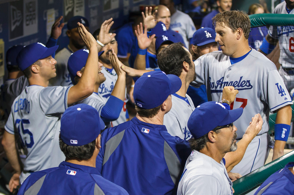 Description of . Los Angeles Dodgers' A.J. Ellis gets congratulations from teammates after scoring on a double by Mark Ellis against Philadelphia Phillies during the seventh inning of a baseball game, Friday, Aug. 16, 2013, in Philadelphia. The Dodgers won 4-0. (AP Photo/Christopher Szagola)