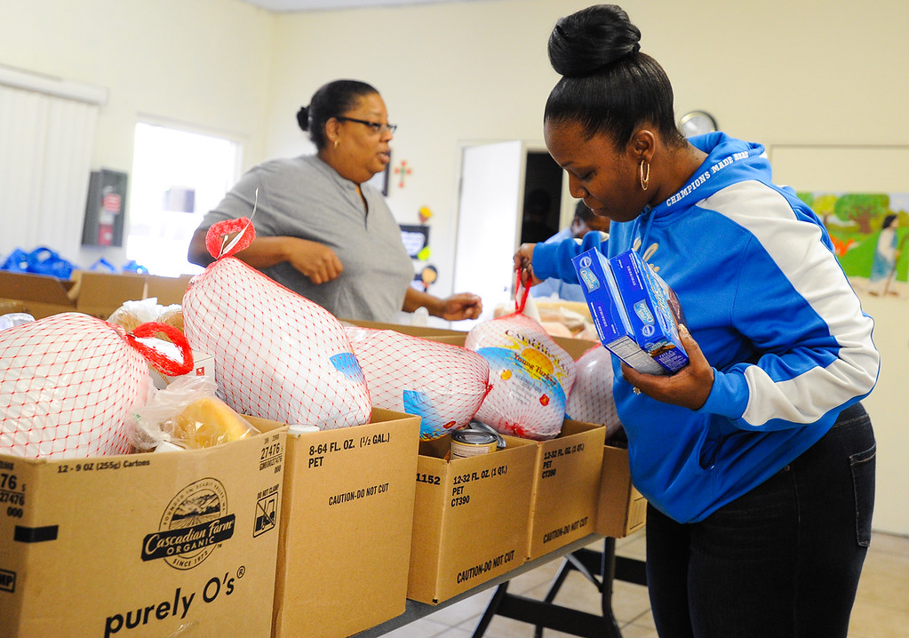 Description of . Church volunteer Nicole Clark, right, and Veronica Buck help put together free Thanksgiving dinner baskets at 16th Street Seventh-day Adventist Church in San Bernardino on Tuesday, Nov. 26, 2013. The church distributed 175 baskets to families-in-need. (Photo by Rachel Luna / San Bernardino Sun)