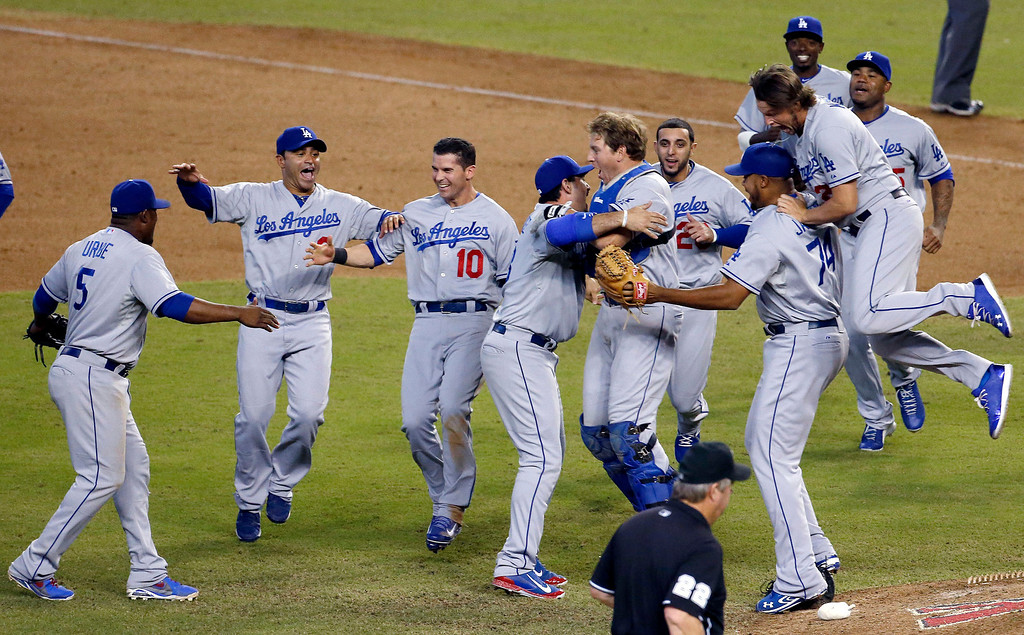 Description of . Los Angeles Dodgers celebrate their win to capture the Western Division National League Championship after a baseball game against the Arizona Diamondbacks, Thursday, Sept. 19, 2013, in Phoenix. The Dodgers won 7-6. (AP Photo/Ross D. Franklin)
