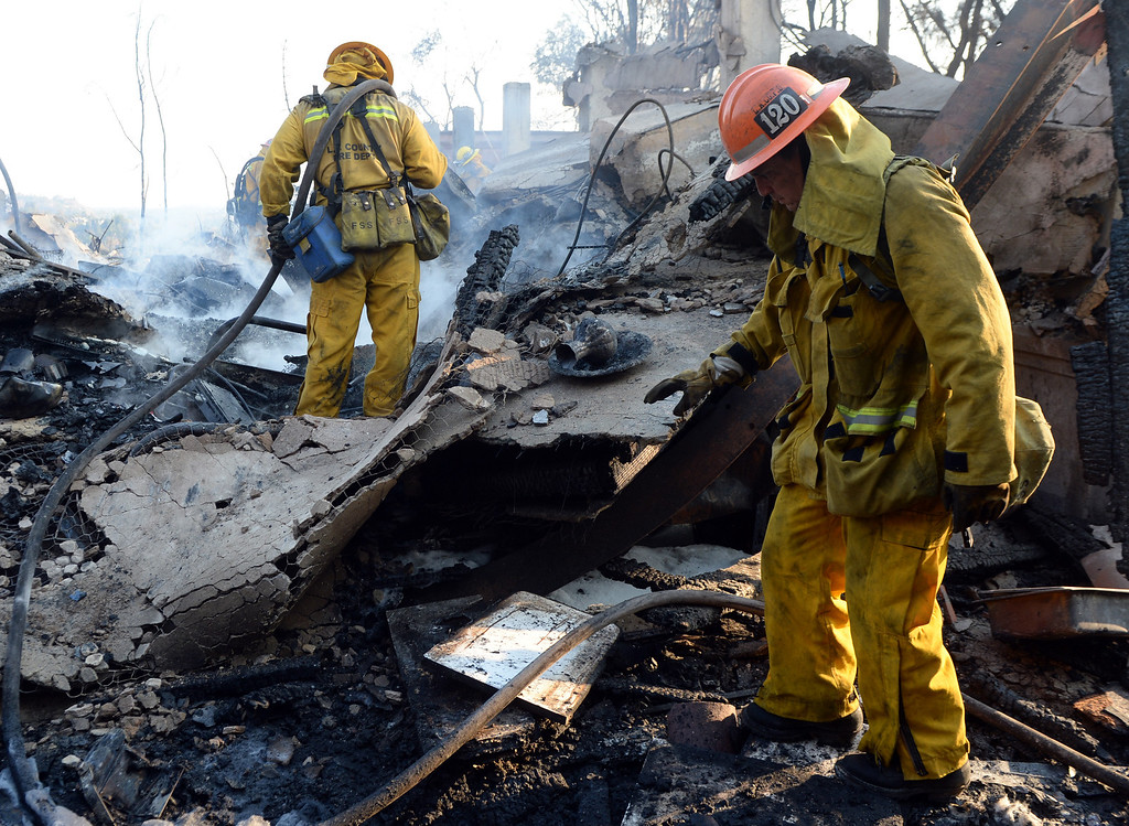 Description of . A Los Angeles County firefighter out of San Dimas and a capt. out of Diamond Bar works on the fire at the Singer Estate a top Kregmont Dr. where a guest home and six car garage burned during the Colby Fire, a 1,700-acre plus brush fire that ignited in the Angeles National Forest north of Glendora  threatening homes and prompting mandatory evacuations in Glendora, Calif., on Thursday, Jan. 16, 2014. (Keith Birmingham Pasadena Star-News)