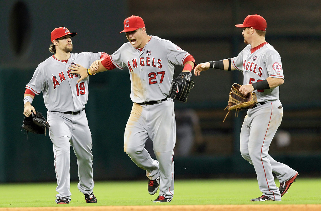 Description of . HOUSTON, TX - SEPTEMBER 14:  Mike Trout #27 of the Los Angeles Angels of Anaheim along with Luis Jimenez #18 and Kole Calhoun #56 celebrate after the final out against the Houston Astros at Minute Maid Park on September 14, 2013 in Houston, Texas.  (Photo by Bob Levey/Getty Images)
