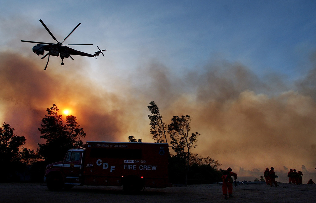Description of . Ten years ago this month the arson caused Old Fire, fanned by Santa Ana winds burned thousands of acres, destroyed hundreds of homes and caused six deaths. The fire burned homes in San Bernardino, Highland, Cedar Glen, Crestline, Running Springs and Lake Arrowhead and forced the evacuation of thousand of residents. A sky crane water dropping helicopter flies over a group of inmate fire fighters from Oak Glen. (Staff file photo/The Sun)