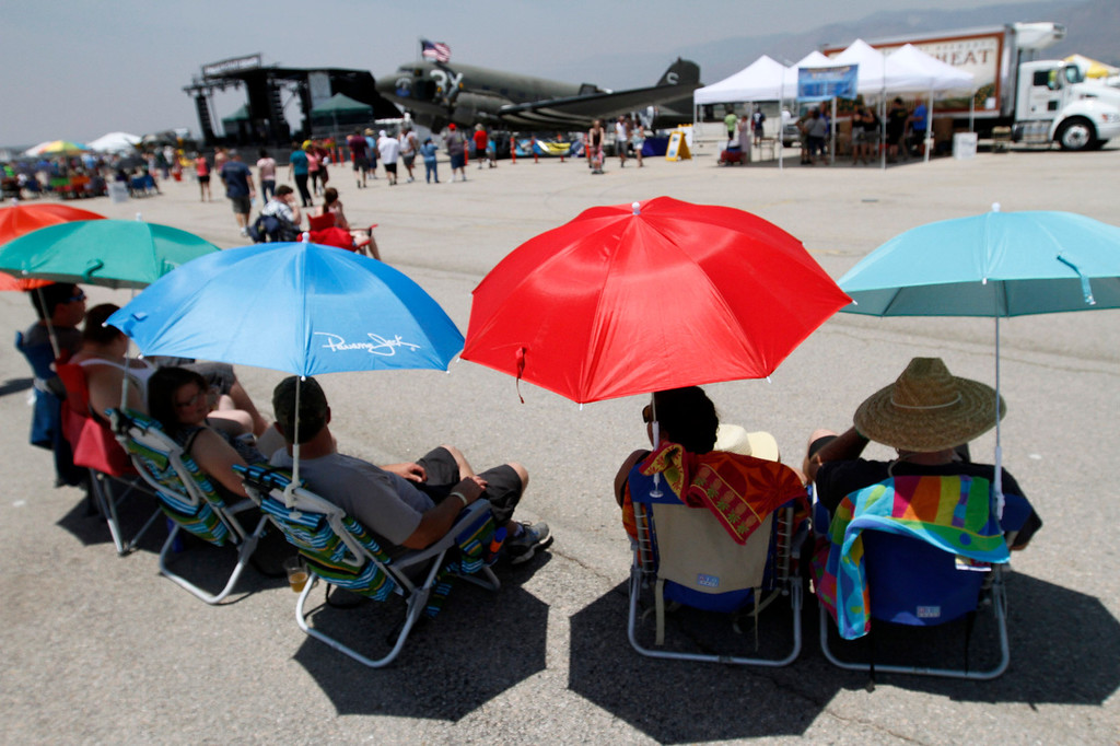 Description of . AirFest attendees relax under umbrellas during the Hangar 24 AirFest and 6th Anniversary Celebration on Saturday, May 17, 2014 at the Redlands Municipal Airport in Redlands, Ca. (Photo by Micah Escamilla/Redlands Daily Facts)
