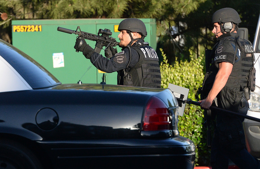 Description of . Ontario police and SWAT members search for a murder suspect in the Camden Land Mark Apartments in Ontario Thursday June 12, 2014 after a man was found shot to death on the apartments property. (Will Lester/Inland Valley Daily Bulletin)