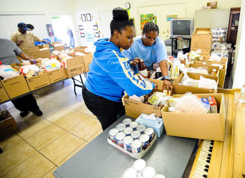 Description of . Church volunteers help pack and hand out free Thanksgiving dinner baskets at 16th Street Seventh-day Adventist Church in San Bernardino on Tuesday, Nov. 26, 2013. The church distributed 175 baskets to families-in-need. (Photo by Rachel Luna / San Bernardino Sun)