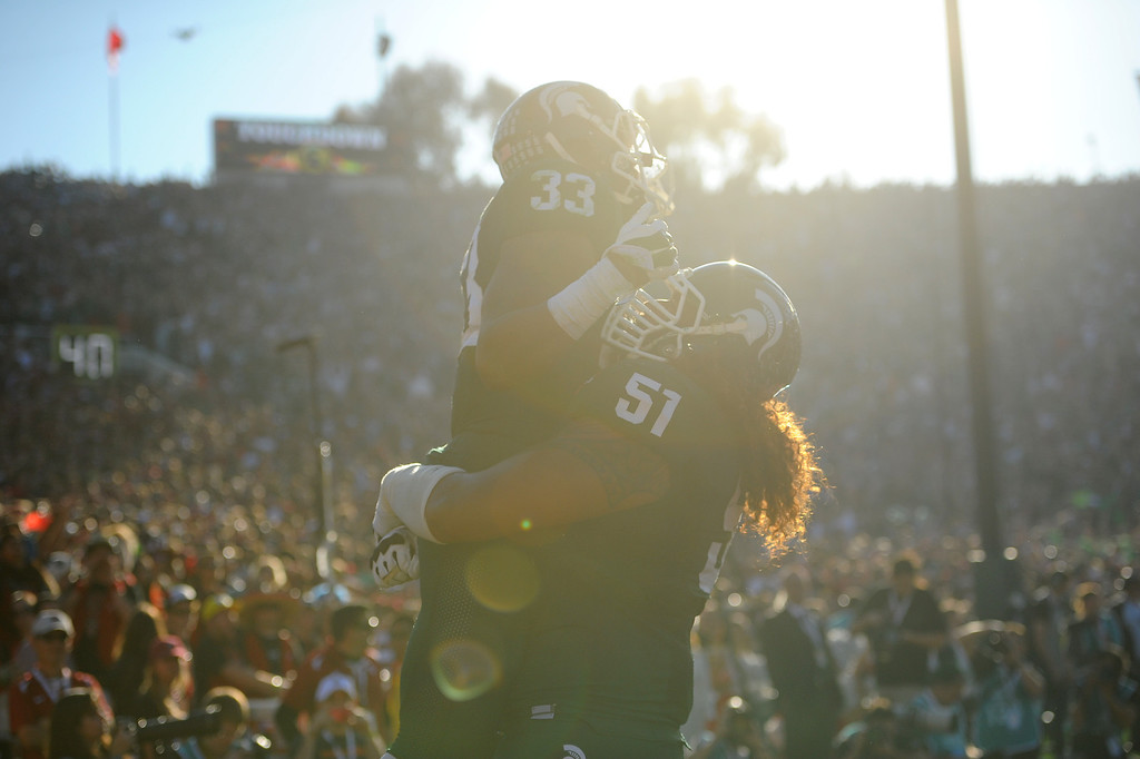 Description of . Michigan State RB Jeremy Langford is lifted up by Fou Fonoti after scoring a touchdown in the second quarter at  the Rose Bowl game, Wednesday, January 1, 2014. (Photo by Michael Owen Baker/L.A. Daily News)