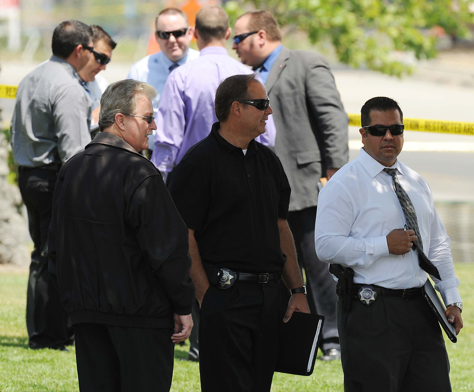 Description of . California Highway Patrol officers and authorities at the scene of an officer-involved shooting on Thursday afternoon in San Bernardino following a car chase on the 10 Freeway. (LaFonzo Carter / Staff Photographer)
